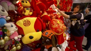 A vendor selling Lunar New Year decorations adjusts a display of stuffed animals at a wholesale market in Beijing on Tuesday, Feb. 13, 2018. (AP Photo/Mark Schiefelbein)