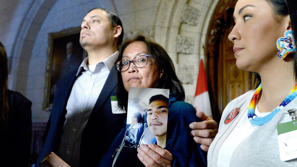 Debbie Baptiste holds up a photo of her son Colten Boushie, as the family spoke to reporters in the Foyer of the House of Commons after a day of meetings on Parliament Hill, in Ottawa on Tuesday, Feb. 13, 2018. (Justin Tang / THE CANADIAN PRESS)