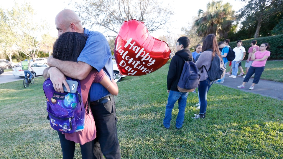Family member embrace following a shooting at Marjory Stoneman Douglas High School, Wednesday, Feb. 14, 2018, in Parkland, Fla. (AP Photo/Wilfredo Lee)