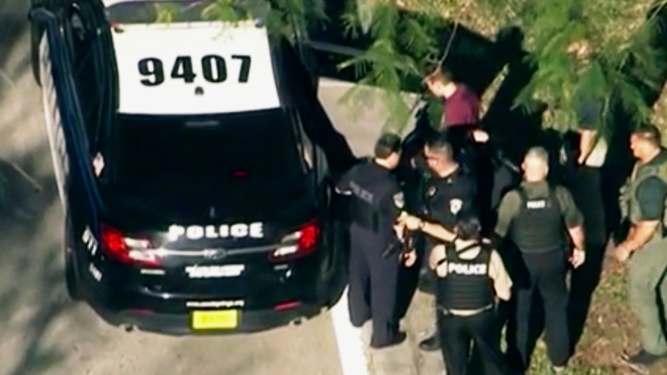 In this frame grab from video provided by WPLG-TV, law enforcement personnel arrest an unidentified man (in dark red), following a shooting at Marjory Stoneman Douglas High School in Parkland, Fla., Wednesday, Feb. 14, 2018. (WPLG-TV via AP)