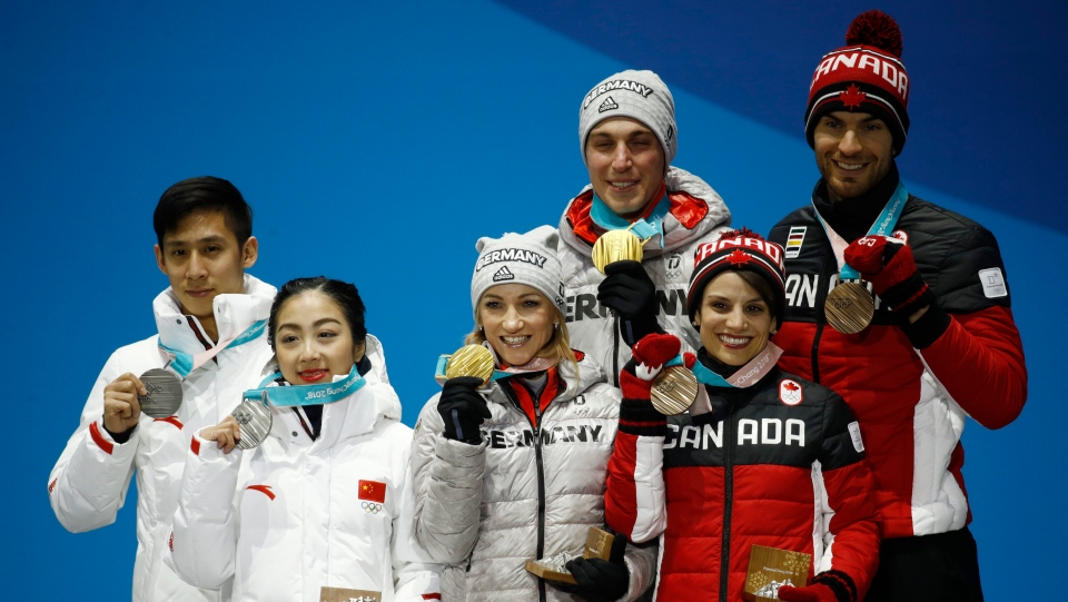 Medalists in the pairs free skate figure skating final left, China's Sui Wenjing and Han Cong, silver, Germany's Aljona Savchenko and Bruno Massot, center, and Canada's Meagan Duhamel and Eric Radford, bronze, pose during their medals ceremony at the 2018 Winter Olympics in Pyeongchang, South Korea, Thursday, Feb. 15, 2018. (AP Photo/Patrick Semansky)