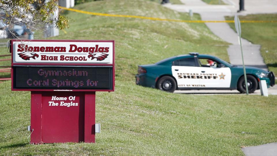 Law enforcement officers block off the entrance to Marjory Stoneman Douglas High School, Thursday, Feb. 15, 2018 in Parkland, Fla. (AP / Wilfredo Lee)