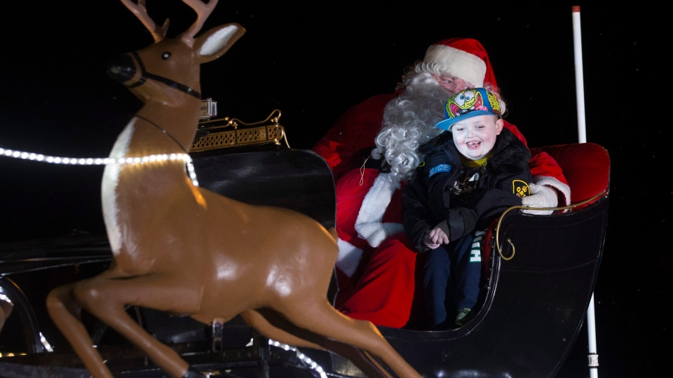 Evan Leversage rides in sleigh at a Christmas Parade in St. George, Ontario on Saturday October 24, 2015. Residents of the local community organized the parade for the seven-year-old boy. THE CANADIAN PRESS/Chris Young
