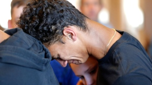 Austin Burden, 17, cries on the shoulder of a friend after a vigil at the Parkland Baptist Church, for the victims of the Wednesday shooting at Marjory Stoneman Douglas High School, in Parkland, Fla., Thursday, Feb. 15, 2018. Nikolas Cruz, a former student, was charged with 17 counts of premeditated murder on Thursday. (AP Photo/Gerald Herbert)
