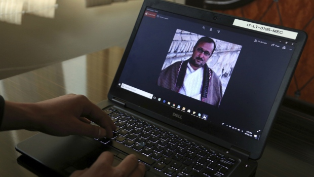 Shoaib shows a picture of his father who along with 13 others were killed in Afghanistan's central Ghor Province by gunmen in 2014, during an interview with The Associated Press in Kabul, Afghanistan on Friday, Feb. 9, 2018. (AP Photo/Rahmat Gul)