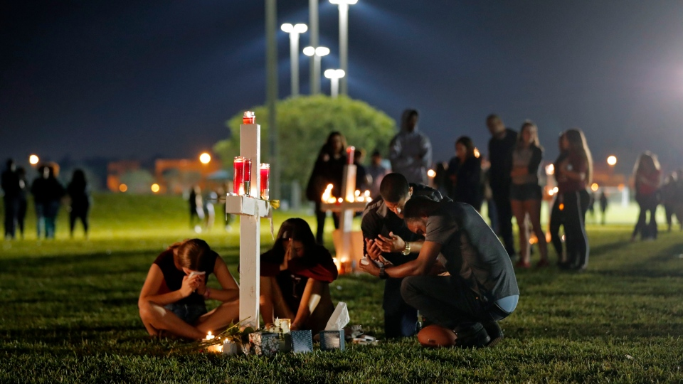 People pray around one of seventeen crosses, after a candlelight vigil for the victims of the Wednesday shooting at Marjory Stoneman Douglas High School, in Parkland, Fla., Thursday, Feb. 15, 2018. (AP Photo/Gerald Herbert)