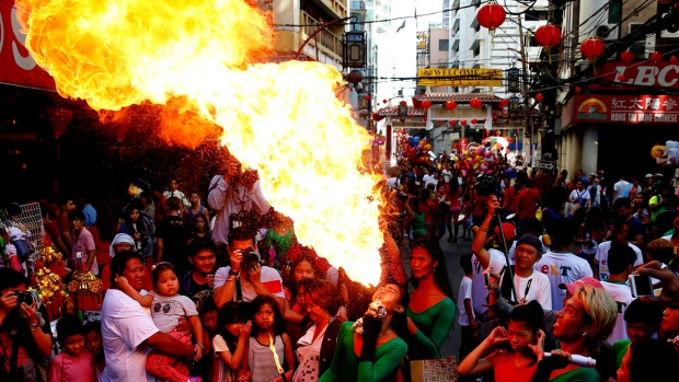 A fire-eater performs on the street in celebration of the Chinese Lunar New Year Friday, Feb. 16, 2018 at Manila's Chinatown district, Philippines. This year is the Year of the Dog in the Chinese Lunar calendar. (AP Photo/Bullit Marquez)