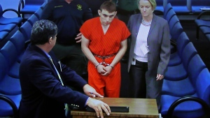 A video monitor shows school shooting suspect Nikolas Cruz, left, with public defender Melisa McNeille, making an appearance before Judge Kim Theresa Mollica in Broward County Court, Thursday, Feb. 15, 2018, in Fort Lauderdale, Fla.  (Susan Stocker/South Florida Sun-Sentinel via AP, Pool)