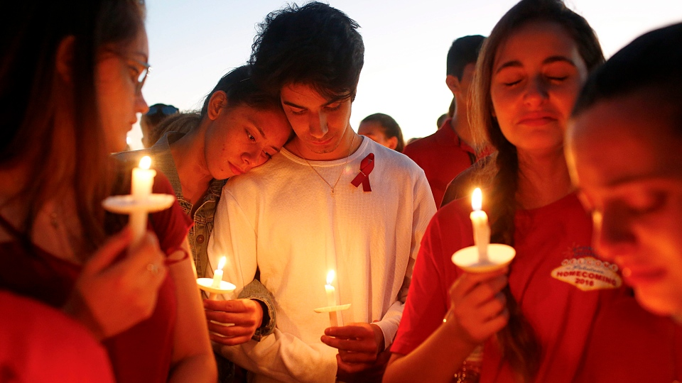 Students gather during a vigil at Pine Trails Park for the victims of the Wednesday shooting at Marjory Stoneman Douglas High School, in Parkland, Fla., Thursday, Feb. 15, 2018. Nikolas Cruz, a former student, was charged with 17 counts of premeditated murder on Thursday. (Brynn Anderson/THE ASSOCIATED PRESS)
