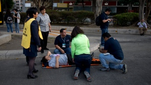 A woman is helped outside, along Reforma Avenue after a 7.2-magnitude earthquake shook Mexico City, Friday, Feb. 16, 2018. (AP Photo/Eduardo Verdugo)