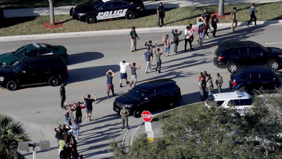 In this Feb. 14, 2018 file photo, students hold their hands in the air as they are evacuated by police from Marjory Stoneman Douglas High School in Parkland, Fla., after a shooter opened fire on the campus. (Mike Stocker/South Florida Sun-Sentinel via AP, File)