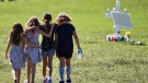 This photo taken Friday, Feb. 16, 2018, shows four young children with hands around each other as they approach a vigil post at Park Trails Park in Parkland, Fla. The park has became a gathering place for the community to honor the 17 students that were killed by a former student at Marjory Stoneman Douglas High School on Valentine's Day. (C.M. Guerrero/The Miami Herald via AP)