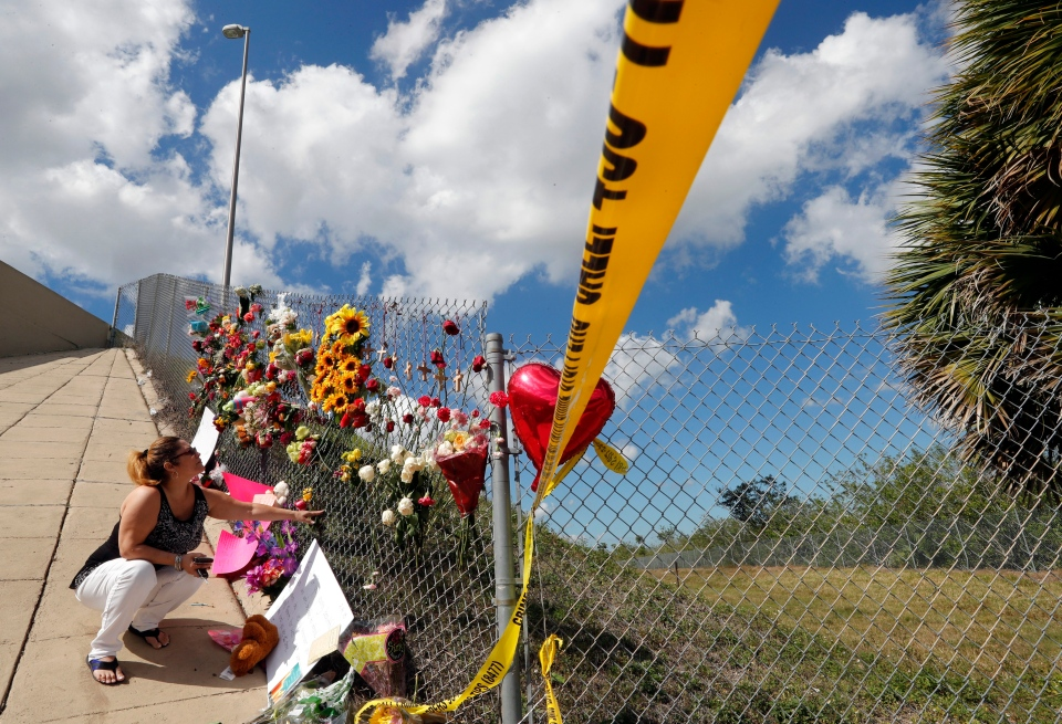 Carrie Hernandez, of Coral Springs, places flowers under an overpass, at the edge of the crime scene, near Marjory Stoneman Douglas High School, where students sought shelter after the Wednesday shooting at the school, in Parkland, Fla., Saturday, Feb. 17, 2018. (Gerald Herbert/AP Photo)