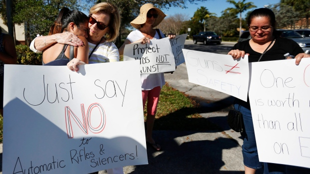 Cathy Kuhns, right, hugs Ana Paula Lopez, left, as they stands on a street corner holding up anti gun signs in Parkland, Fla., on Saturday, Feb. 17, 2018.  (AP Photo / Brynn Anderson)