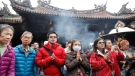 People pray for good luck during the Lunar NewYear at the Lonshan Temple in Taipei, Taiwan, Saturday, Feb. 17, 2018. (AP Photo/Chiang ying-ying)
