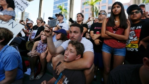 Louis Reinstein, embraces his son, Daniel, 10, during a protest against guns on the steps of the Broward County Federal courthouse in Fort Lauderdale, Fla., on Saturday, Feb. 17, 2018. (AP Photo / Brynn Anderson)