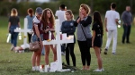 People pay homage at the memorial crosses for the 17 deceased students and faculty from the Wednesday shooting at Marjory Stoneman Douglas High School, in Parkland, Fla., Friday, Feb. 16, 2018. (AP Photo/Gerald Herbert)