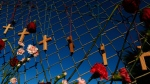 Crosses and flowers hang on a fence near Marjory Stoneman Douglas in Parkland, Fla., on Saturday, Feb. 16, 2018, in memory of the 17 people killed in a school shooting on Wednesday. As families began burying their dead, authorities questioned whether they could have prevented the attack at the high school where a gunman, Nikolas Cruz, took several lives. (AP Photo/Brynn Anderson)