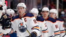 Edmonton Oilers center Connor McDavid is congratulated as he passes the team box after scoring his first of two goals in the third period against the Colorado Avalanche, Sunday, Feb. 18, 2018, in Denver. (AP Photo/David Zalubowski)