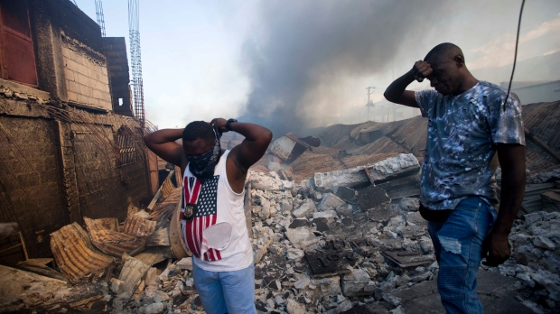 A vendors covers his nose and mouth with a bandana next to another vendor amid the ruins of the biggest clothing market as it burns in Port-au-Prince, Haiti, Sunday, Feb. 18, 2018. (AP Photo/Dieu Nalio Chery)