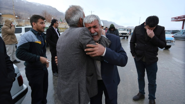 In this photo provided by Tasnim News Agency, family members of a plane crash victims weep in the village of Bideh, at the area that the plane crashed, southern Iran, Sunday, Feb. 18, 2018. (Ali Khodaei/Tasnim News Agency via AP)
