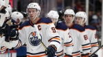 Edmonton Oilers centre Connor McDavid, front, is congratulated as he passes the team box after scoring his first of two goals in the third period of an NHL hockey game in Denver against the Colorado Avalanche, Sunday, Feb. 18, 2018. (AP Photo/David Zalubowski)