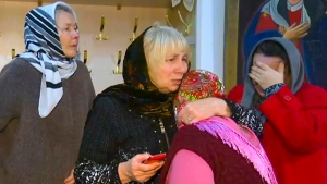 In this video grab provided by the RU-RTR Russian television a group of believers comfort each other after a memorial service in the Russian Orthodox Church in Kizlyar, Russia, Monday, Feb. 19, 2018. (RU-RTR Russian Television via AP)