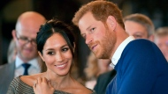 FILE - In this Thursday Jan. 18, 2018 file photo, Britain's Prince Harry talks to Meghan Markle as they watch a dance performance by Jukebox Collective in the banqueting hall during a visit to Cardiff Castle, Wales. With Prince Harry and Meghan Markle's May 19 wedding fast approaching, the fashion and bridal worlds are abuzz with talk of who the bride will pick to design her dress and what kind of look she would go for. (Ben Birchall/Pool via AP, File)
