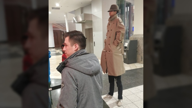 Two men disguised as one very tall man stand in line for 'Black Panther' in Carson, Calif., on Feb. 16, 2018. (Twitter / @stevelikescups)