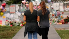 Sara Smith, left, and her daughter Karina Smith visit a makeshift memorial outside the Marjory Stoneman Douglas High School, where 17 students and faculty were killed in a mass shooting on Wednesday, in Parkland, Fla., Monday, Feb. 19, 2018. Nikolas Cruz, a former student, was charged with 17 counts of premeditated murder on Thursday. (AP Photo/Gerald Herbert)