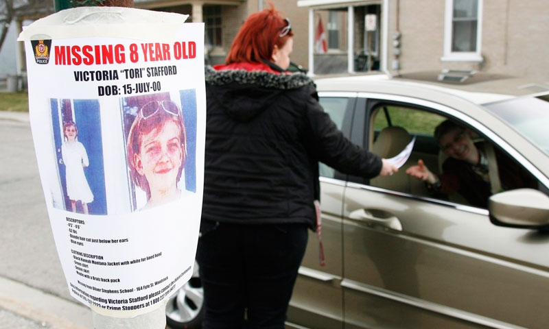 Tiffany Ackers hands out a poster for missing Victoria 'Tori' Stafford, 8, on a street corner in Woodstock, Ont. on Friday April 10, 2009. THE CANADIAN PRESS/Dave Chidley