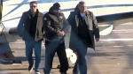 Stephane Parent is escorted from a plane by RCMP after landing in Calgary to face a second-degree murder charge in the death of Adrienne McColl