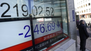 A man uses a smartphone in front of an electronic stock indicator of a securities firm in Tokyo, Tuesday, Feb. 20, 2018. (AP Photo/Shizuo Kambayashi)