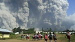 School children walk as Mount Sinabung erupts in Karo, North Sumatra, Indonesia on Monday, Feb. 19, 2018. (AP Photo/Sarianto)