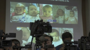 Media attend a press briefing where Thai police display projected pictures of surrogate babies born to a Japanese man who is at the centre of a surrogacy scandal during a press conference at the police headquarters in Chonburi, Thailand on Aug. 12, 2014. (AP Photo/Sakchai Lalit)