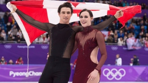 Ice dance gold medalists Canada's Tessa Virtue and Scott Moir skate with the Canadian flag during victory ceremonies at the Pyeongchang Winter Olympics Tuesday, February 20, 2018 in Gangneung, South Korea. THE CANADIAN PRESS/Paul Chiasson