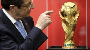 Cyprus' President Nicos Anastasiades examines the FIFA World Cup trophy in Larnaca, Cyprus, on Feb. 16, 2018. (Petros Karadjias / AP)