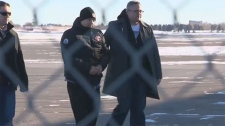 Stephane Parent is escorted by police at the Calgary Airport and has been charged with second-degree murder in the death of Adrienne McColl.