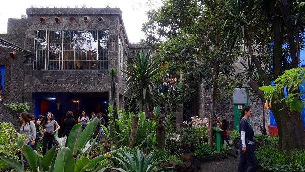 In this July 28, 2016 photo, tourists walk the extensive gardens at La Casa Azul, the Museo Frida Kahlo, where artists Frida Kahlo and Diego Rivera lived and worked in Mexico City. (AP Photo/Ross D. Franklin)