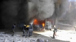 Members of the Syrian Civil Defense extinguishing a store during airstrikes and shelling by Syrian government forces, in Ghouta, a suburb of Damascus, Syria, Tuesday, Feb. 20, 2018. (Syrian Civil Defense White Helmets via AP)