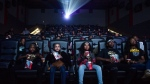 Mari Copeny, third from left, watches a free screening of the film 'Black Panther' with more than 150 children, after she raised $16,000 to provide free tickets in an entire theater on Monday, Feb. 19, 2018 in Flint Township, Mich. (Jake May /The Flint Journal-MLive.com via AP)