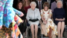 Britain's Queen Elizabeth, second left, sits next to fashion editor Anna Wintour, second right, and Caroline Rush, chief executive of the British Fashion Council (BFC), left, as they view Richard Quinn's runway show before presenting him with the inaugural Queen Elizabeth II Award for British Design, as she visits London Fashion Week's BFC Show Space in central London, Tuesday, Feb. 20, 2018. (Yui Mok/Pool photo via AP)