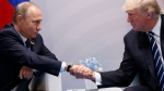 In this Friday, July 7, 2017 file photo U.S. President Donald Trump shakes hands with Russian President Vladimir Putin at the G20 Summit in Hamburg. (Evan Vucci/AP Photo)