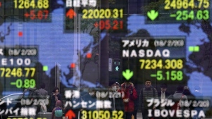 People are reflected on an electronic stock indicator of a securities firm in Tokyo, Wednesday, Feb. 21, 2018. (AP Photo/Shizuo Kambayashi)