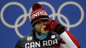 Gold medallist in the men's ski cross Brady Leman, of Canada, kisses his medal during the medals ceremony at the 2018 Winter Olympics in Pyeongchang, South Korea on Wednesday, Feb. 21, 2018. (AP Photo/Charlie Riedel)