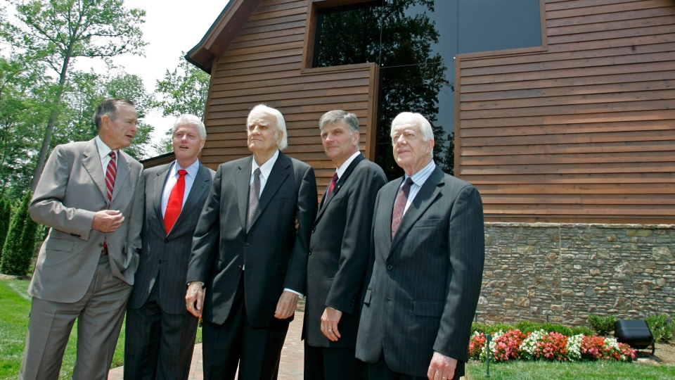 In this May 31, 2007 file photo, former U.S. Presidents, George H.W. Bush, left, Bill Clinton, second left, and Jimmy Carter, right, join Franklin Graham, second right, as they pose with Billy Graham, center, in front of the Billy Graham Library in Charlotte, N.C. (AP / Chuck Burton, File)
