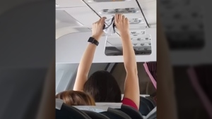 A woman dries out a pair of underwear on a commercial flight in this image taken from YouTube video.