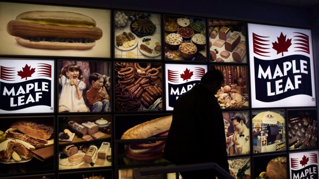 A Maple Leaf Foods employee walks past a Maple Leaf sign at the company's meat facility in Toronto on Monday, December, 15, 2008. (THE CANADIAN PRESS/Nathan Denette)