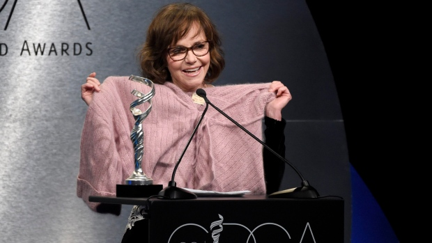 """Sally Field holds up a sweater worn by her character in """"Forrest Gump"""" as she presents the career achievement award at the 20th annual Costume Designers Guild Awards at The Beverly Hilton hotel on Tuesday, Feb. 20, 2018, in Beverly Hills, Calif. (Photo by Chris Pizzello/Invision/AP)"""