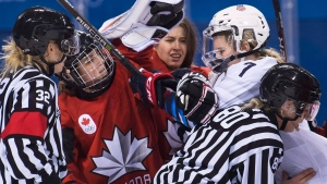 Canada forward Marie-Philip Poulin (29) battles with United States forward Monique Lamoureux-Morando (7) as Canada goaltender Genevieve Lacasse, centre, had her helmet taken off during third period women's olympic hockey action at the 2018 Olympic Winter Games in Gangneung, South Korea on Thursday, February 15, 2018. THE CANADIAN PRESS/Nathan Denette